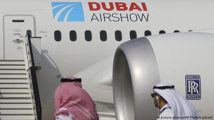 Арабские посетители перед самолетом с надписью Dubai Airshow