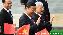 Chinese President Xi Jinping, center, and Vietnam Communist Party General Secretary Nguyen Phu Trong, right, wave during a welcoming ceremony at the presidential palace in Hanoi, Vietnam Sunday, Nov. 12, 2017. (Hoang Dinh Nam/Pool Photo via AP)  