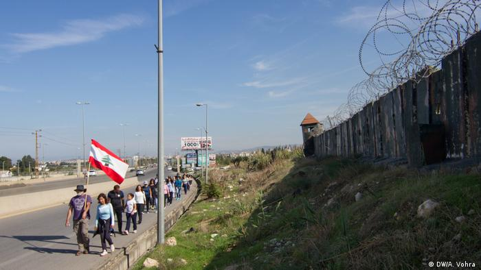 A group of walkers walk down a road holding a Lebanese flag