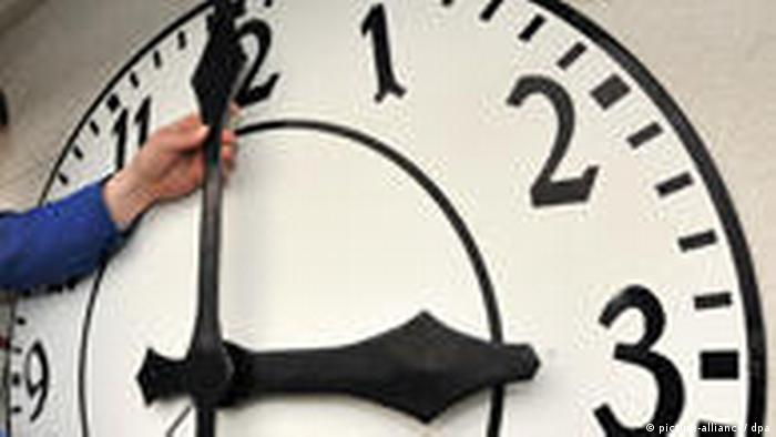 Man changing the hands of a clock to 3 (picture-alliance/ dpa)