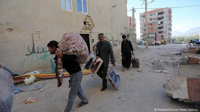 People carry their belongings on their backs and in suitcases through the rubble of Sarpol-e Zahab. (Reuters/Tasnim News Agency )
