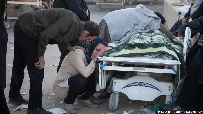 An Iranian woman cries next to a dead body lying on a stretcher. (Reuters/Tasnim News Agency)