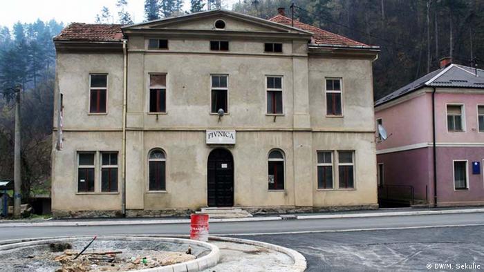 Prédio cinza de dois andares com várias janelas e uma porta