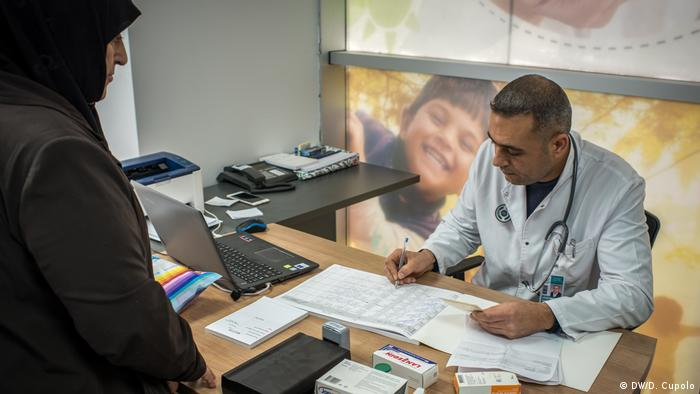 Dr. Nidal Ozturk receives a patient in his office at the Altindag Bab-i Sifa migrant health center