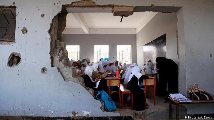 Buraco na parede deixa entrever crianças em sala de aula bombardeada em cidade do Iêmen