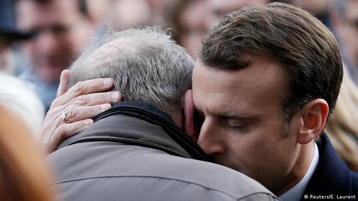 Macron comforts a mourning man (Reuters/E. Laurent)