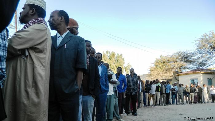 Men queue at a polling station