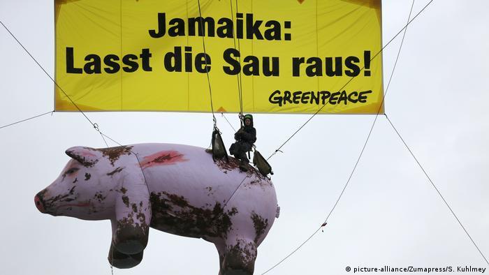 Greenpeace flies a sign over a giant pig criticizing German politicians