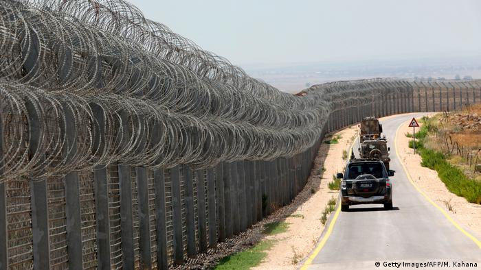 A convoy of vehicles drives down a road next to a razor wire fence