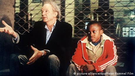 Film scene of Figures of the Night with an older man and a refugee boy, both sitting (picture-alliance/dpa/Peter Rommel Film)
