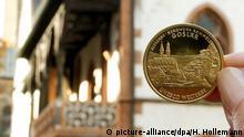 ARCHIV- Eine 100-Euro-Goldmünze der Unesco «Weltkulturerbe Erzbergwerk Rammelsberg und Altstadt Goslar» wird vor dem Rathaus der Stadt am nördlichen Harzrand präsentiert. Vor 25 Jahren wurden das Erzbergwerk Rammelsberg und die Altstadt von Goslar zum Weltkulterbe ernannt. (zu dpa Goslar feiert 25 Jahre Welterbe vom 14.11.2017) Foto: Holger Hollemann/dpa +++(c) dpa - Bildfunk+++   Verwendung weltweit