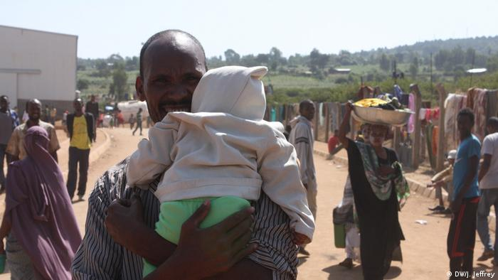 A man carries a baby on the run from ethnic violence in Ethiopia (DW/J. Jeffrey)