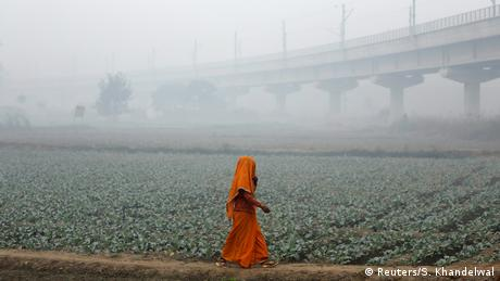 A woman walks across a field on a smoggy morning in New Delhi, India (Reuters/S. Khandelwal)