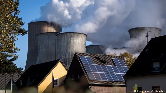 Coal-fired power plant next to roof with solar panels