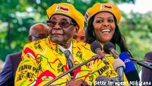 Zimbabwe's President Robert Mugabe (L) addresses party members and supporters gathered at his party headquarters to show support to Grace Mugabe (R) becoming the party's next Vice President after the dismissal of Emerson Mnangagwa November 8 2017. Zimbabwe's sacked vice president, Emmerson Mnangagwa, said on November 8, 2017, he had fled the country, as he issued a direct challenge to long-ruling President Robert Mugabe and his wife Grace. / AFP PHOTO / Jekesai NJIKIZANA (Photo credit should read JEKESAI NJIKIZANA/AFP/Getty Images)