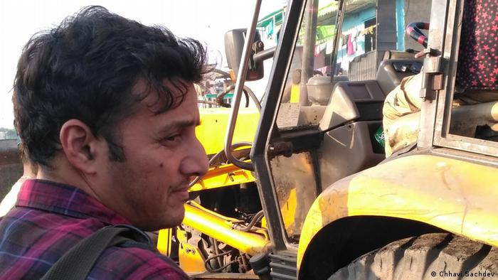 Afroz Shah next to a tractor