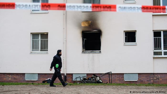 A security guard walks past a blackened window