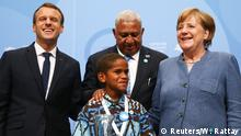 15.11.2017 *** French President Emmanuel Macron, COP23 President Prime Minister Frank Bainimarama of Fiji and German Chancellor Angela Merkel pose for a photo with Timothy Naulusala from Fiji during the COP23 U.N. Climate Change Conference in Bonn, Germany, November 15, 2017. REUTERS/Wolfgang Rattay
