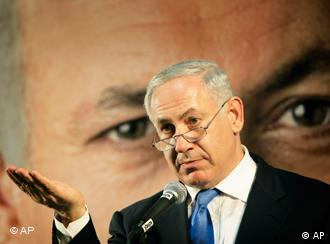 Portrait of Benjamin Netanyahu standing in front of a blown-up photograph of Benjamin Netanyahu
