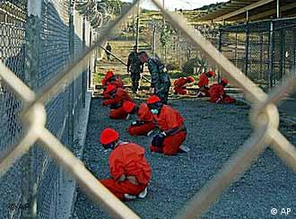 Wearing orange suits and blindfolded, Guantanamo detainees kneel before a wire fence