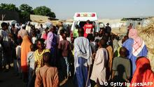 October 23, 2017. Onlookers stand as ambulance carries dead bodies recovered from the scene of three suicide bomb blasts that left 13 people dead in Maiduguri, northeast Nigeria, on October 23, 2017. Three female suicide bombers killed 13 people and wounded 16 in the northeastern city of Maiduguri on ctober 22, 2017, security sources said.The first bomber detonated her explosive belt in front of a small restaurant in the capital of Borno state when people were buying their dinner, a military source said on condition of anonymity. The two other bombers followed minutes later. The Boko Haram conflict has left at least 20,000 dead and forced more than 2.6 million others to flee their homes since 2009. / AFP PHOTO / STRINGER (Photo credit should read STRINGER/AFP/Getty Images)