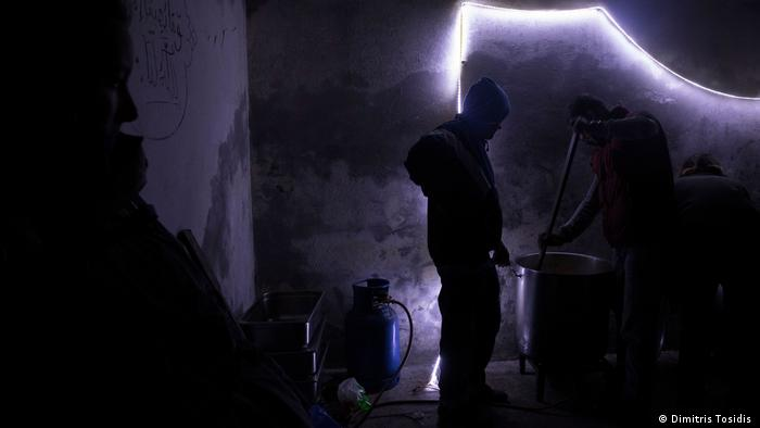 A man preparing food in an abandoned factory
