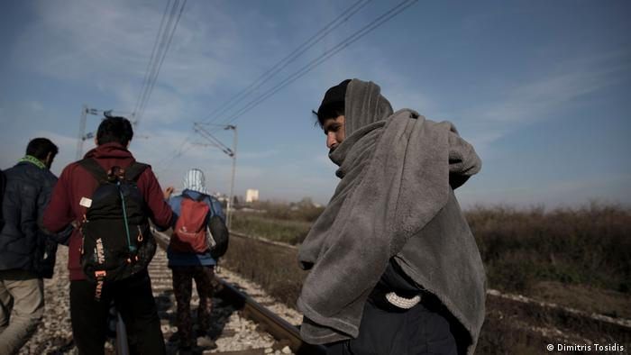 A group of refugees walking along train tracks
