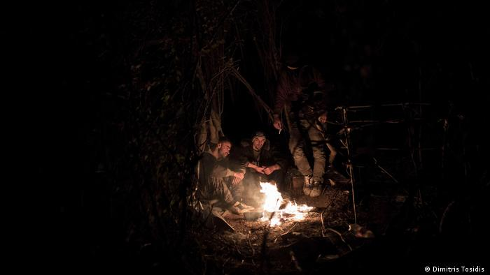 A group of migrants around a fire