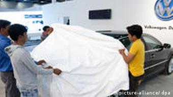 staff in VW plant remove cover from car