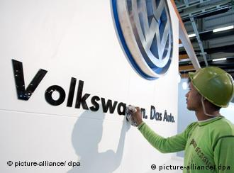 A worker at Volkswagen's new Indian plant dusts a sign with the firm's logo