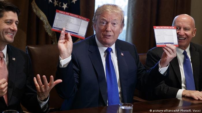 Donald Trump raises a new tax form mockup during a meeting on tax policy