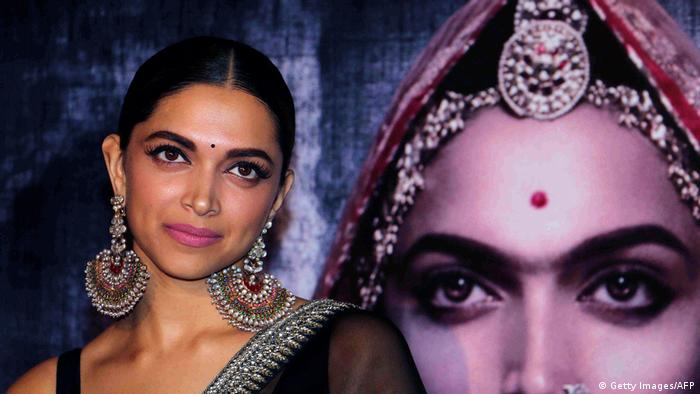 Deepika Padukone posing in front of a large movie poster