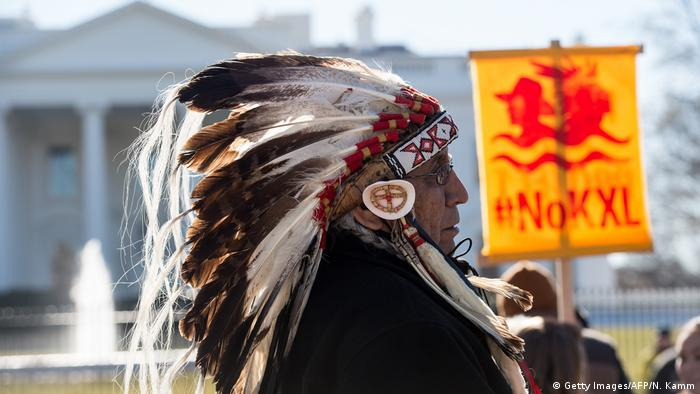 Native American man wearing a feathered headress in front of the White House