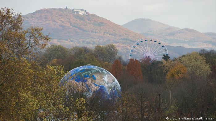 A globe among trees with ferris wheel in the background at the COP23 climate conference