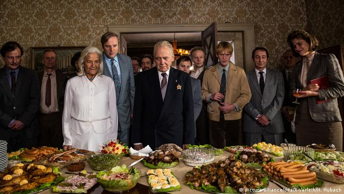 A family gathers in a room and stars at a bountiful buffet on a table