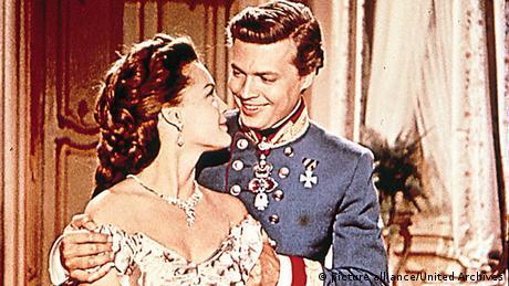 """21.12.1955. u Beču je bila premijera filma """"Sisi"""" o Austrijskoj carici Elizabeti. Mnogi to delo vide kao savršeni kič. Sa Romi Šnajder i Karl-Hajnc Bemom u glavnim ulogama, snimljena su ukupno tri filma o """"Sisi"""". Šnajder je odbila četvrti nastavak, uprkos ponuđenim milionima. 1972 je ponovo glumila Sisi, ali tada u Viskontijevom filmu o bavarskom kralju Ludvigu II kojeg je glumio Helmut Berger."""