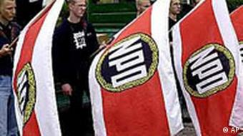 Men hold NPD flags during a rally