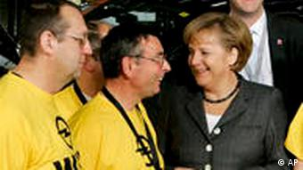 German Chancellor Angely Merkel chatting with Opel employees.