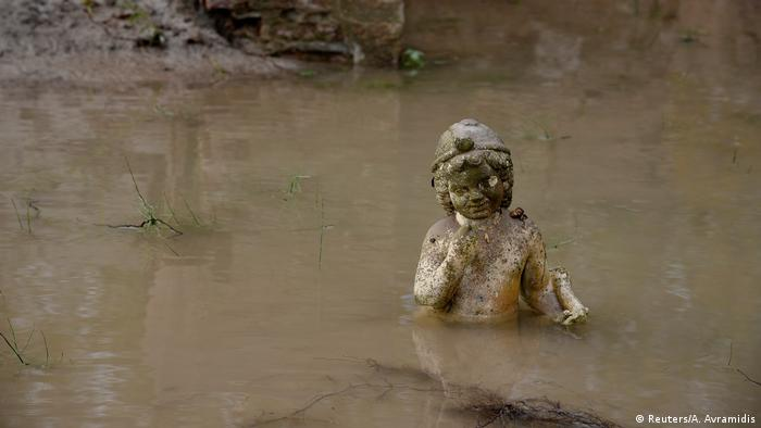 An ancient statue is chest-deep in flood waters.