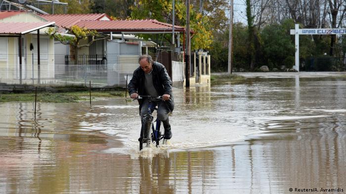 Man riding bicycle through floodwaters in Variko