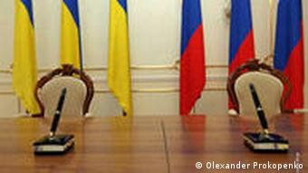 Ukranian and Russian flags behind negotiating table