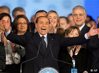 Berlusconi surrounded by women on stage at a congress