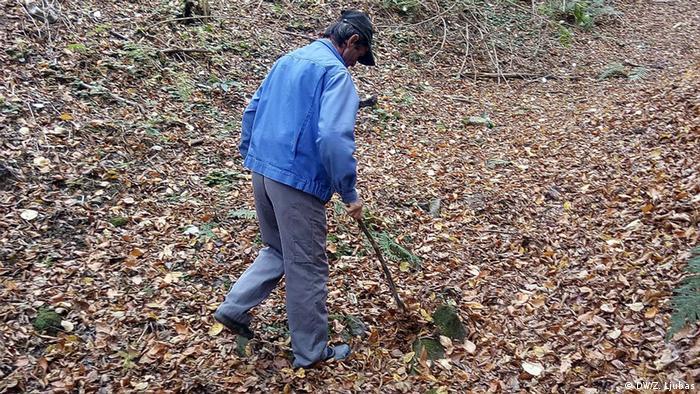 Ramiz searching for bones using a stick