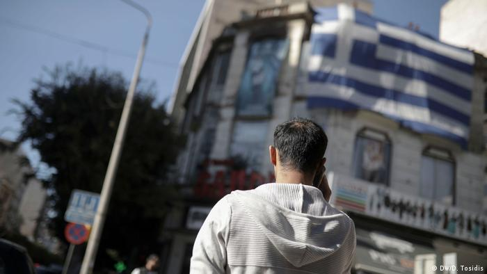 Mohammed speaks to his smuggler on the phone on a street in Greece