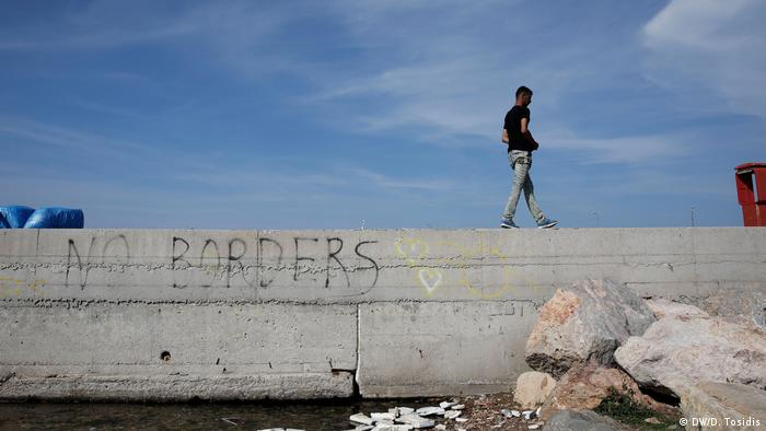 Mohammed walks along a bulkhead sprayed with graffiti that reads 'No borders' on the Greek island of Chios