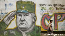 A woman walks past a mural of Bosnian Serb wartime general Ratko Mladic in Belgrade