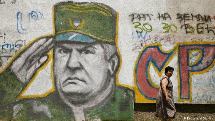 A woman walks past a mural of Bosnian Serb wartime general Ratko Mladic in Belgrade