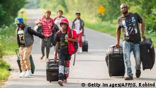 04.08.2017 TOPSHOT - A group of people who claimed to be from Haiti walk down Roxham road in Champlain, New York as they prepare to cross the border into Canada illegally on August 4, 2017. Migrants have been crossing the border in greater numbers in recent weeks. / AFP PHOTO / Geoff Robins (Photo credit should read GEOFF ROBINS/AFP/Getty Images)