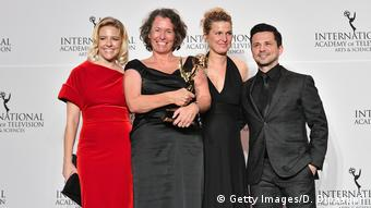 Producers holding trophy at International Emmy Awards in New York