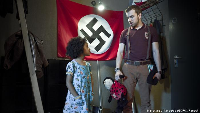 Filim still shows man with child in front of WW2 flag